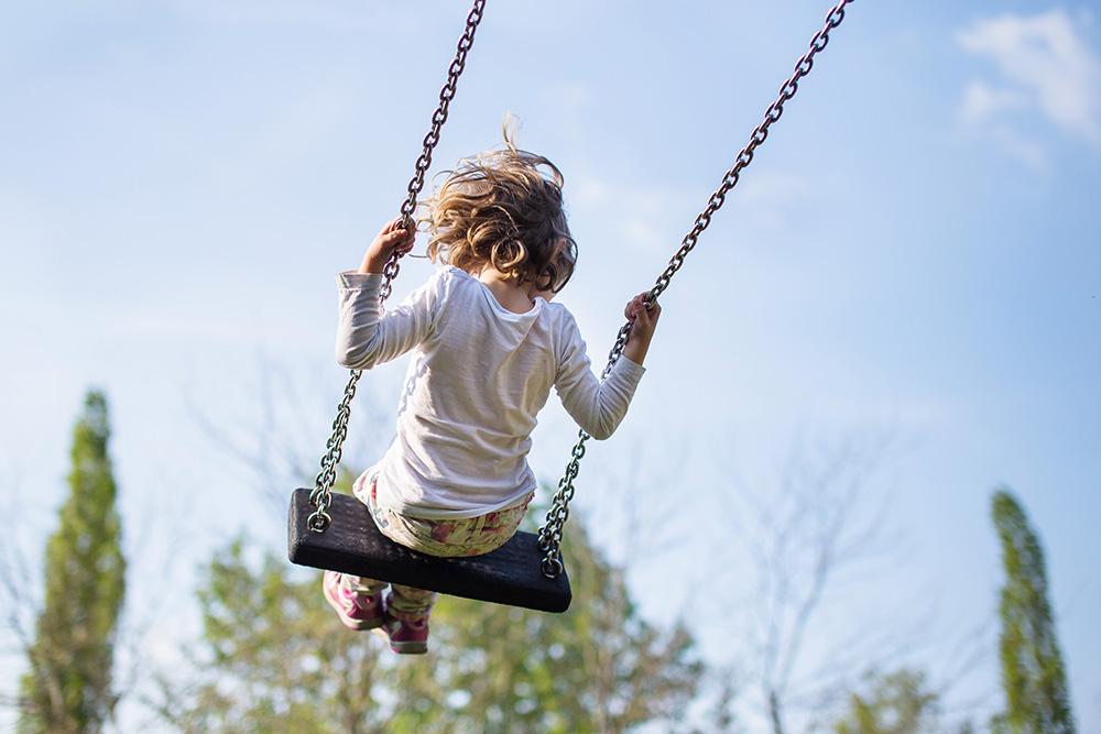 girl on swingset playground