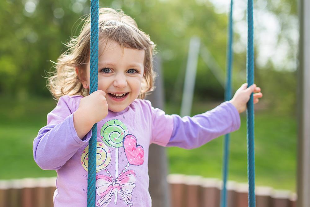Lea climbing on playground happy