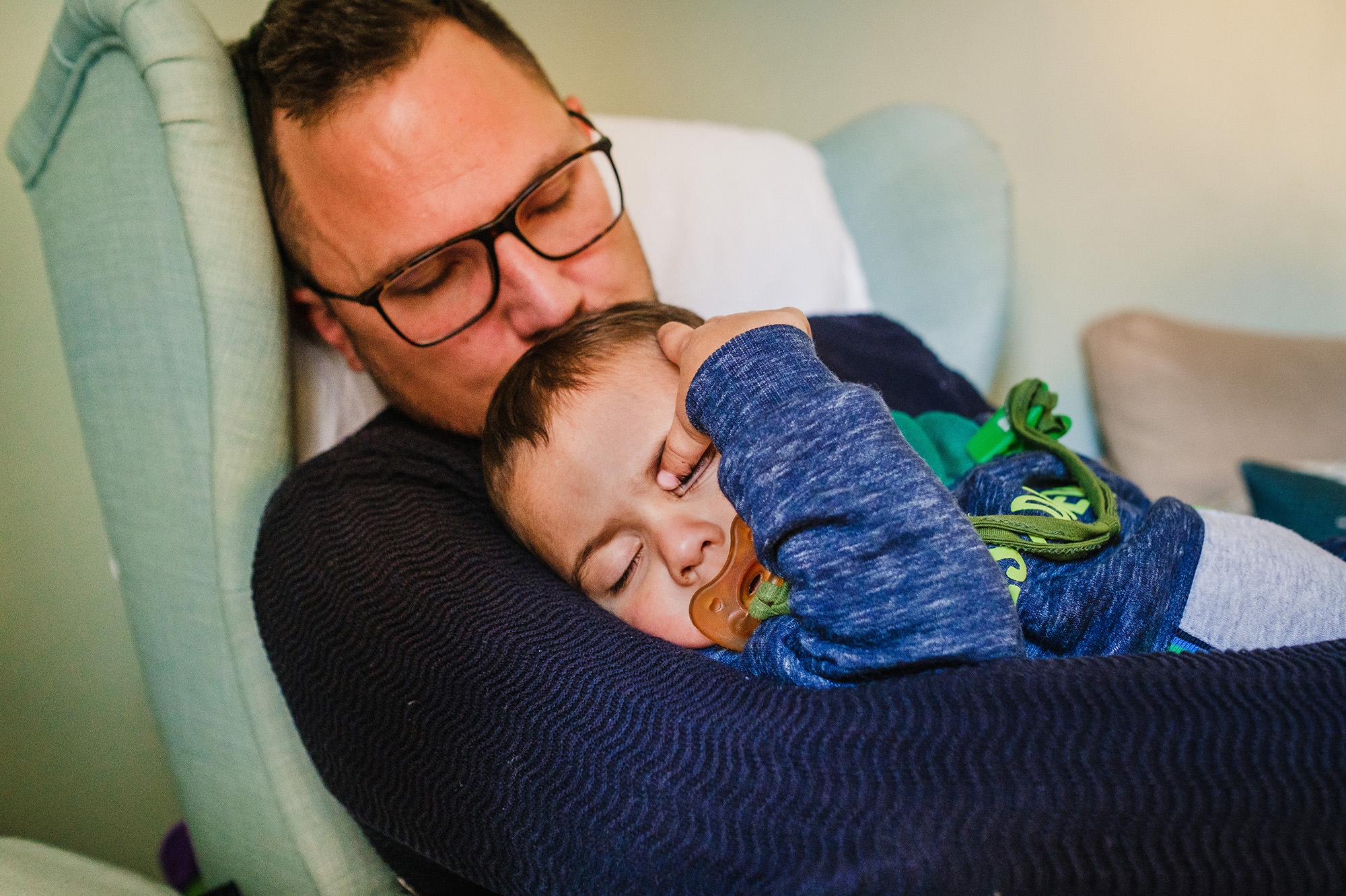 toddler sleeping in daddys arms