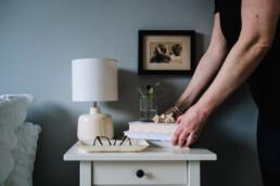 hands arranging details on nightstand