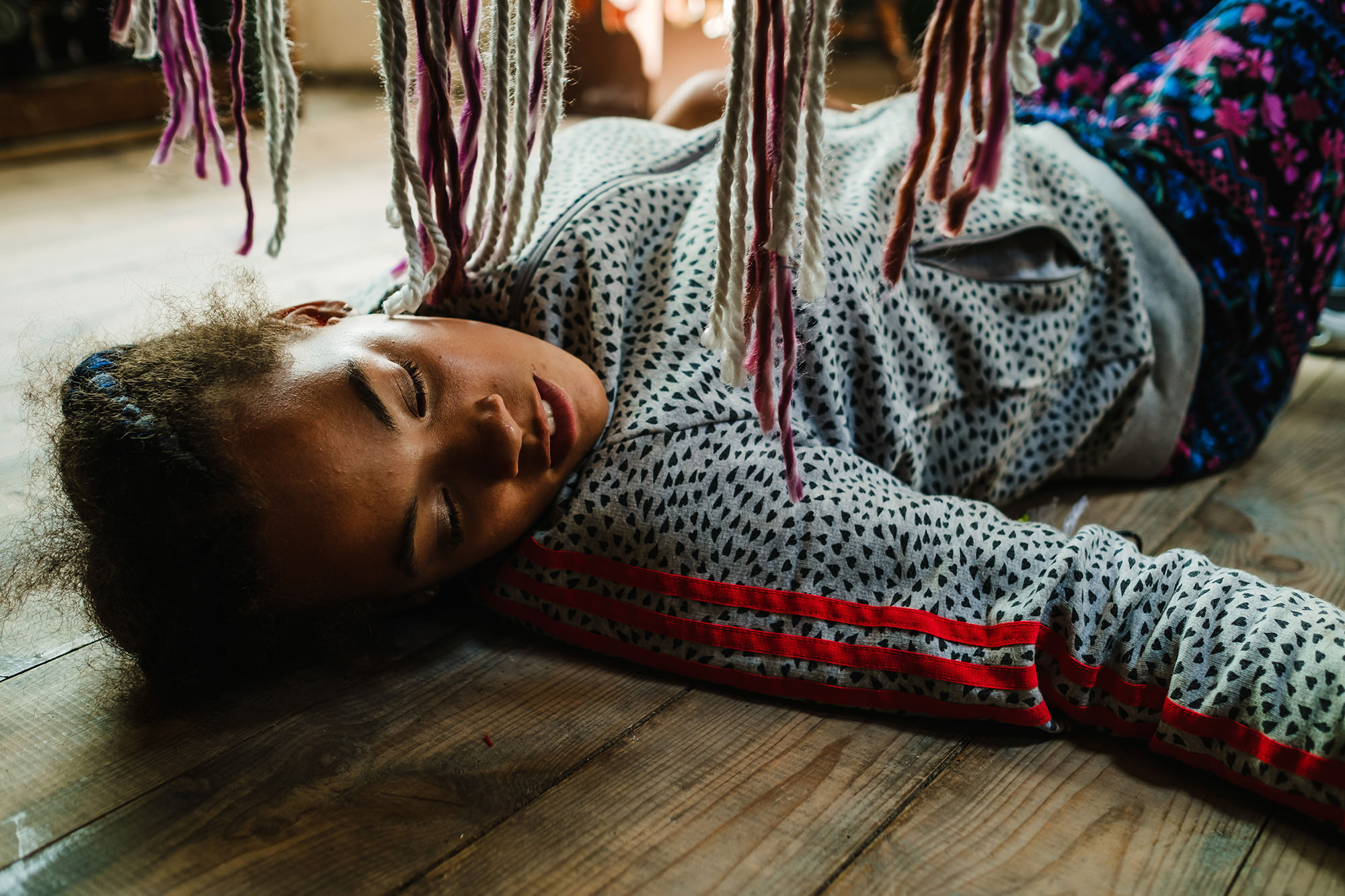 Halle on the floor with a hanging rug