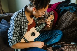 L playing ukulele at home