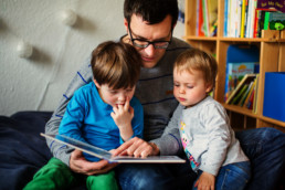 dad reading books with toddler girl and son