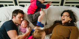jumping on parnets bed family photo shoot