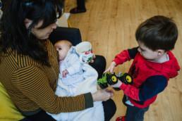 mum feeding baby and minding toddler son